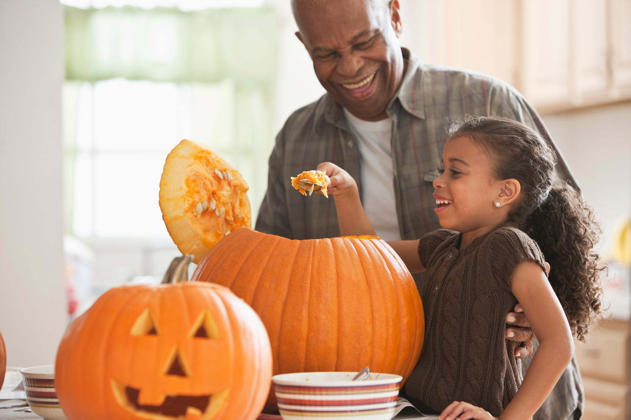grandfather and granddaughter carving a pumpkin