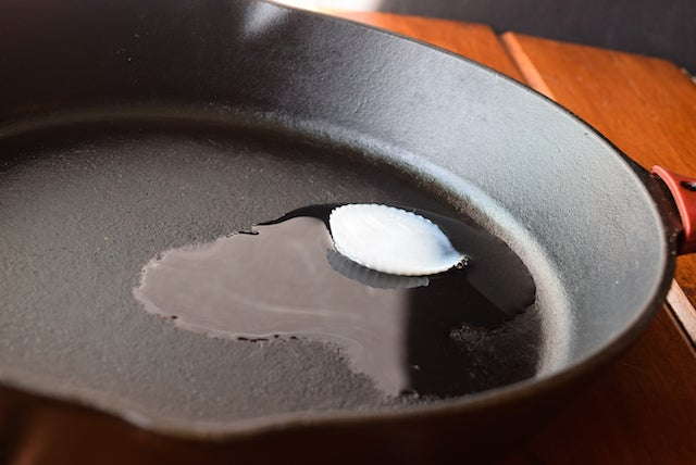 frozen coconut oil cube melting in frying pan skillet